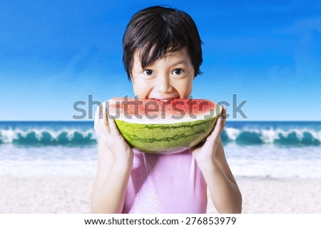 Portrait of beautiful little girl eating a fresh watermelon on the beach while wearing swimsuit - stock photo