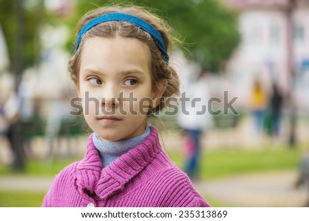 Portrait of beautiful little girl in purple sweater on background of autumn park. - stock photo