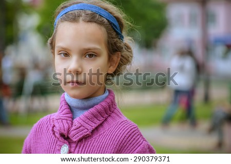 Portrait of beautiful little girl in purple sweater on background of autumn park.