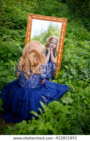 Portrait of beautiful little girl in the blue dress in nature with a mirror