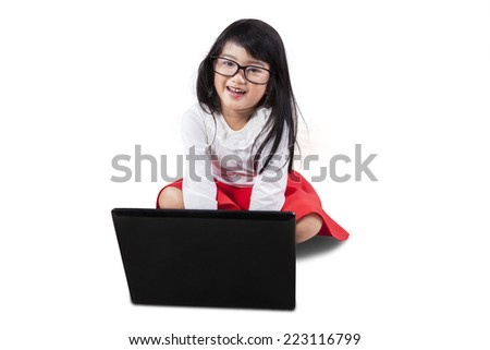 Portrait of beautiful little girl using laptop computer, isolated over white background - stock photo