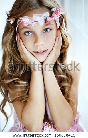 Portrait of beautiful little girl wearing floral wreath - stock photo