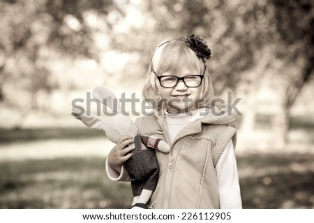 Portrait of  beautiful little girl wearing spectacles outdoors - stock photo