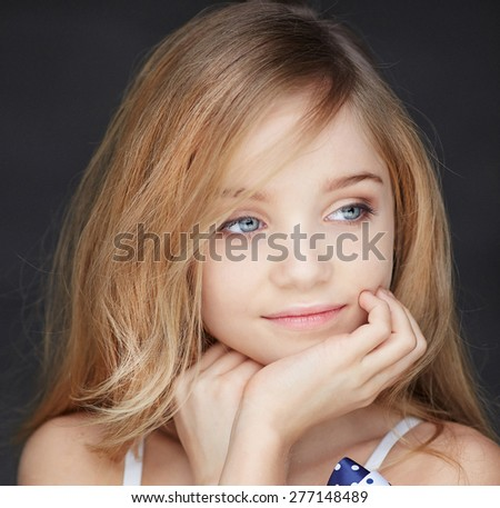 Portrait of beautiful little girl with blond hair on grey background - stock photo