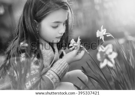 Portrait of beautiful little girl with brownish blond hair and blue eyes standing outdoor on natural background. She is smelling flowers. - stock photo