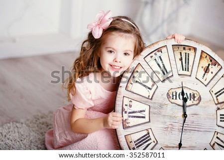 Portrait of Beautiful little girl with long curly hair in pink dress with a big clock waiting for the new year. New year preparation