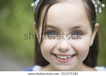 Portrait of beautiful little smiling female kid with long brunette hair in white blouse looking forward standing sunny day outdoor on natural background closeup, horizontal picture - stock photo