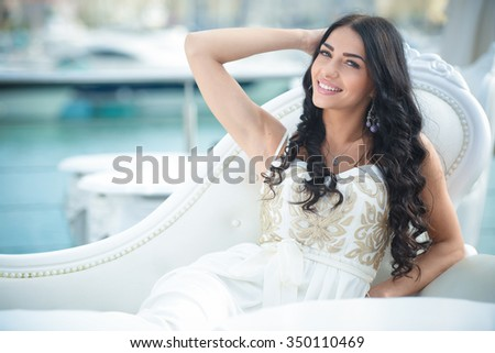 Portrait of beautiful long haired female with charming smile sitting on elegant white sofa outdoor enjoying summer day on copy space background - stock photo