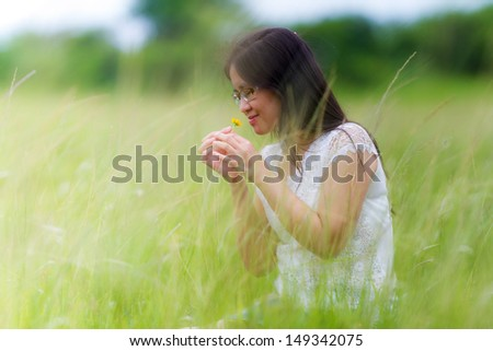 Portrait of beautiful long-haired woman in park and smelling flowers