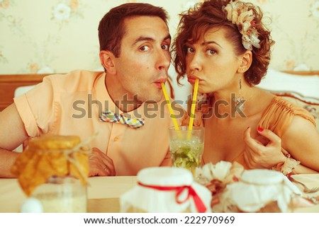 Portrait of beautiful married couple of hipsters in trendy clothing drinking mojito through yellow sippers in vintage cafe. Butterfly accessories. Wedding day. Close up. Indoor shot