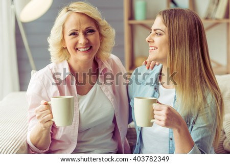 Portrait of beautiful mature mother and her daughter holding cups, looking at camera and smiling, sitting on sofa at home - stock photo