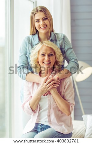 Portrait of beautiful mature mother and her daughter hugging, looking at camera and smiling, sitting on sofa at home - stock photo