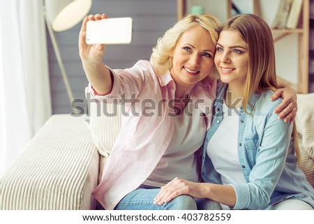 Portrait of beautiful mature mother and her daughter making a selfie using a smart phone and smiling, sitting on sofa at home - stock photo