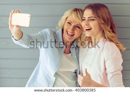 Portrait of beautiful mature mother and her daughter making a selfie using smart phone and smiling, against gray background