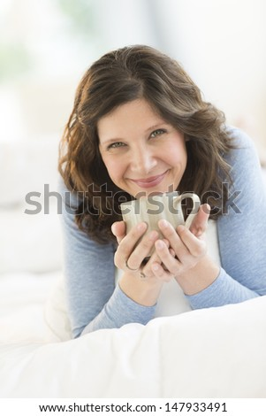 Portrait of beautiful mature woman holding coffee mug while relaxing in bed at home - stock photo