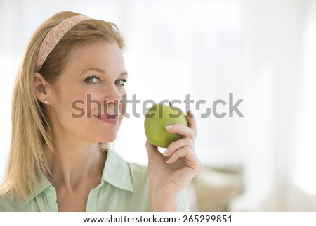 Portrait of beautiful mature woman holding granny smith apple at home - stock photo