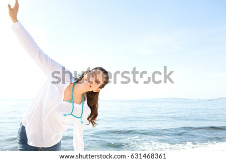 Portrait of beautiful mature woman raising arms up against blue sky, play fun, smiling in coastal sea exterior, outdoors. Dreamy positive joyful female enjoying healthy lifestyle, dynamic in exterior.