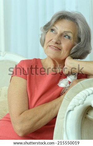 Portrait of beautiful mature woman sitting in vintage sofa