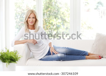 Portrait of beautiful mature woman smiling while sitting at sofa at home.  - stock photo