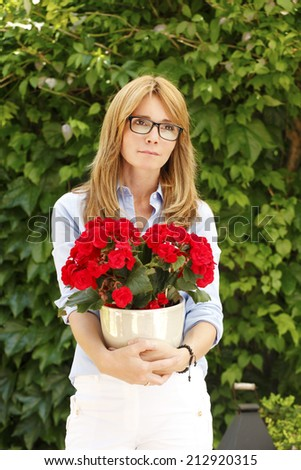 Portrait of beautiful mature woman standing in garden, while holding flower,  - stock photo