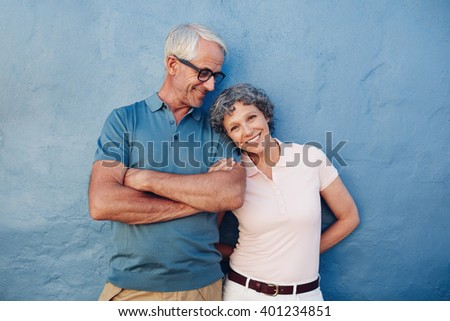 Portrait of beautiful mature woman standing with her husband against blue background. Loving mature couple standing together against a blue wall. - stock photo