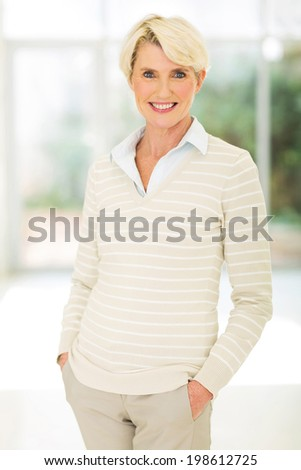 portrait of beautiful mid age woman standing indoors - stock photo