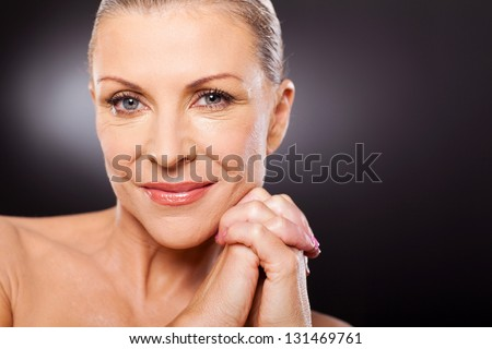 portrait of beautiful mid aged woman close up over black background - stock photo