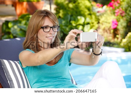Portrait of beautiful middle age woman sitting and taking self portrait at  garden. - stock photo