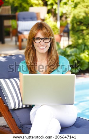Portrait of beautiful middle age woman sitting with laptop in garden. Working at home.