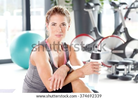 Portrait of beautiful middle age woman taking a break from her fitness workout and drinking protein shake.  - stock photo