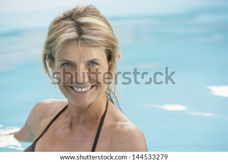 Portrait of beautiful middle aged woman in swimwear swimming in pool
