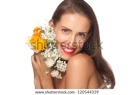 Portrait of beautiful middle aged woman with smooth healthy skin holding flowers. Lady with red lipstick