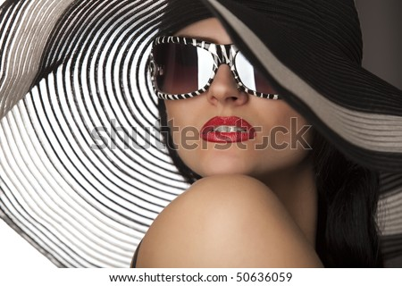 Portrait of beautiful model in striped hat with glasses - stock photo
