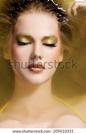 portrait of beautiful model in water with golden make-up, long eyelashes and wet long hair.