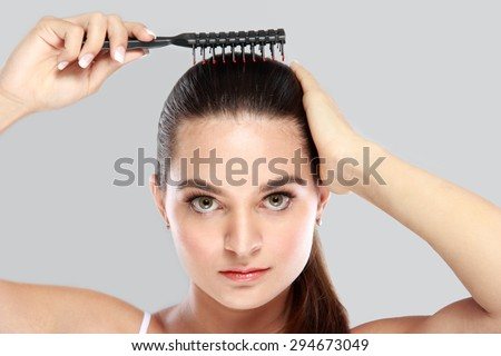 portrait of beautiful model tidy up her hair using hair comb - stock photo