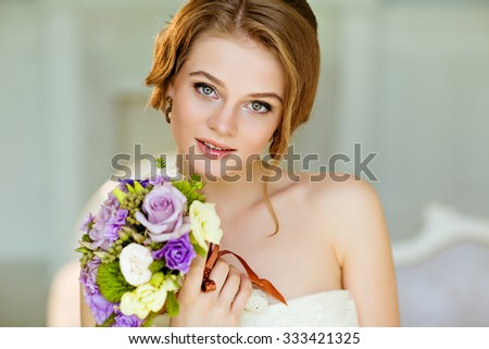 Portrait of beautiful modest shy and very cute girl with brown hair and light eyes with a bouquet of flowers in Studio, close-up - stock photo