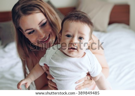 Portrait of beautiful mom playing with her 4 months old baby in bedroom
