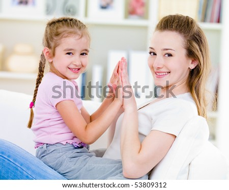 Portrait of beautiful mother and daughter with happy smile  - indoors