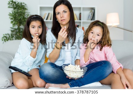 Portrait of beautiful mother and her daughters eating popcorns at home. - stock photo