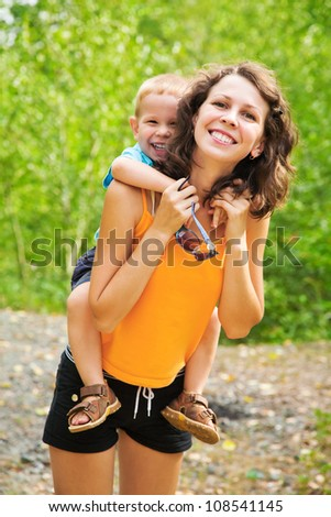 Portrait of beautiful mother holding her son on back outdoor - stock photo