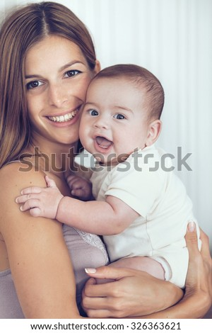 Portrait of beautiful mother kissing her 5 months old baby - stock photo