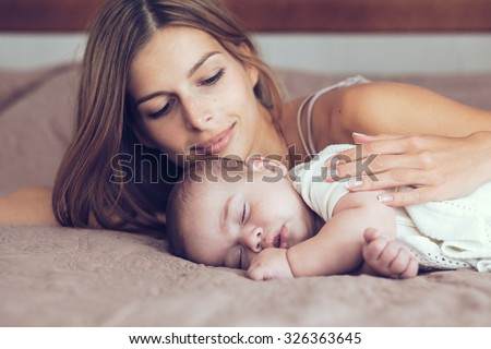 Portrait of beautiful mother with her 5 months old baby sleeping in the bed - stock photo