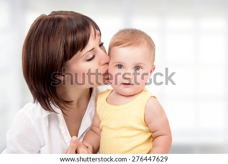 Portrait of beautiful mother with pleasure kissing her cute adorable little daughter at home, happy young family, love and happiness concept