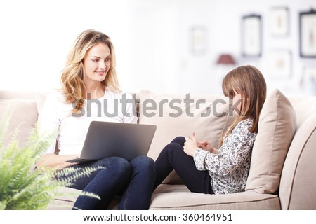 Portrait of beautiful mother working on laptop at home while her cute daughter sitting next to her on sofa and using mobile phone.