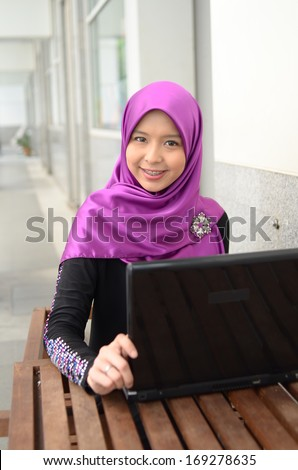 Portrait of beautiful muslim women typing on laptop - stock photo