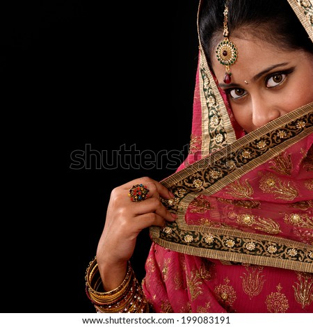 Portrait of beautiful mystery young Indian woman covering her face by veil, looking at camera, copy space at side, isolated on black background.