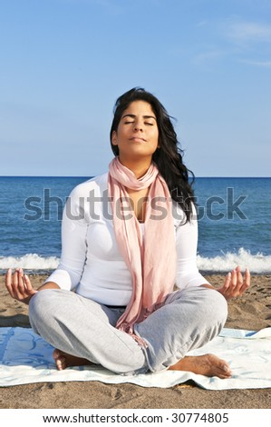Portrait of beautiful native american girl doing yoga at beach