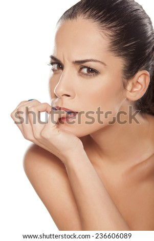Portrait of beautiful nervous woman biting her nails - stock photo