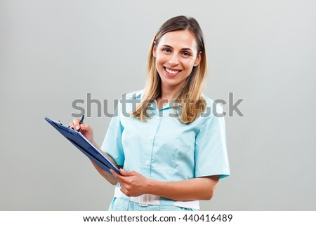 Portrait of beautiful nurse writing notes.Beautiful nurse writing notes - stock photo