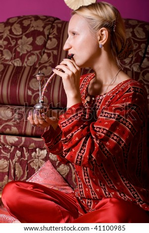 Portrait of beautiful oriental dressed woman with mini hookah - stock photo